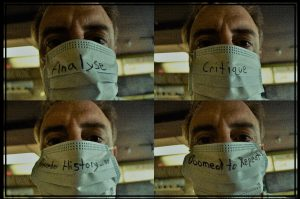 """Jonathan Roberts wearing a face mask with the message """"analyse, critique, remember history... or doomed to repeat"""""""