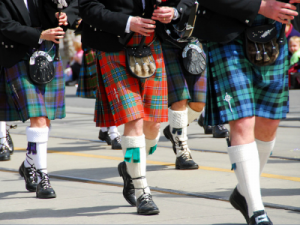 people walking in Scottish kilts with bagpipes