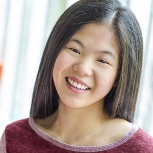 Picture of Emily, a Chinese-Canadian with dark brown hair woman smiling and wearing a red shirt.