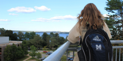 A student looking at the MSVU campus with the text Mount 101 in the background