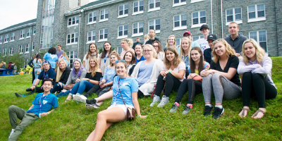 A group of students sitting outside of Evaristus Hall