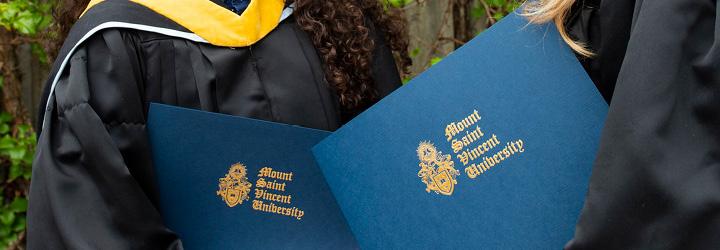 MSVU Graduates holding their degrees outside of Seton Academic Centre