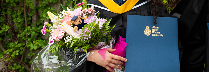 A graduate holding their degree and a bouquet of flowers