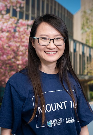 Image of Christina, a Chinese woman wearing a blue Mount 101 t-shirt and glasses standing in the Centre for Academic Advising and Student Success