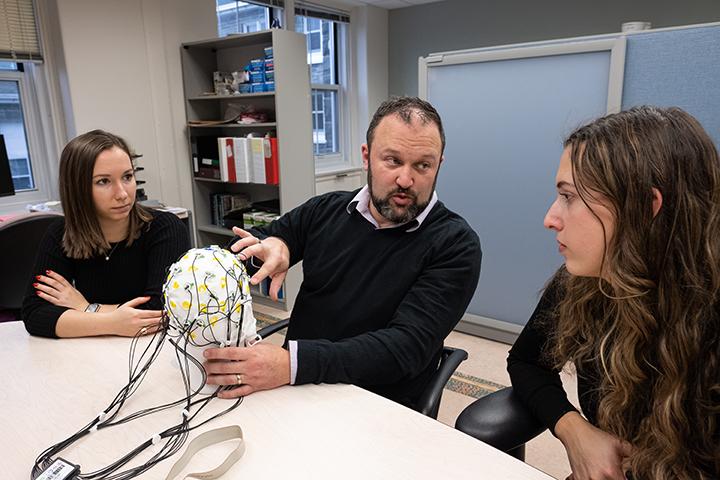 Derek Fisher holding brain scan model in EEG lab