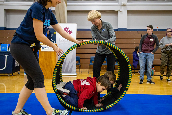 President Bluechardt helping two PACE participants with one of the new pieces of equipment