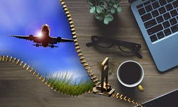 Image of airplane, laptop, coffee, reading glasses