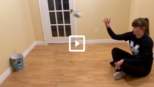 Woman playing a game of sock basketball throwing a sock into a bin