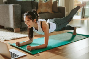woman doing yoga at home with a computer