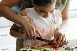 Child and adult cutting vegetables