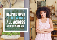 "A women standing beside a sign that reads ""Helping over 13,000 women across Atlantic Canada"""