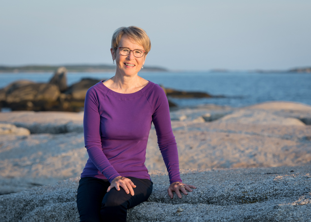 Gina Brown is pictured sitting on a rock by the ocean.